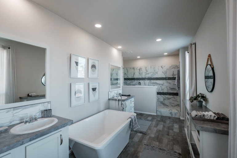 Modern Pre-built modular manufactured home bathroom with soaker tub and 80' tile shower